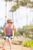 Boy at swings. Positive little boy being playful at swings and enjoying summer vacation at kauai, hawaii Stock Image