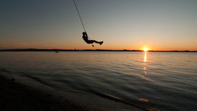 Boy swings from rope over Lake Champlain in Vermont at sunset Royalty Free Stock Image