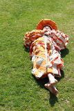 Boy with sword lying on the grass. Little boy in landsknecht clothes with sword lying on green grass Stock Image