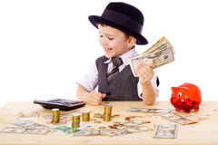 Boy at the table counts money. Little boy in black hat and tie at the table counts money, isolated on white Royalty Free Stock Image