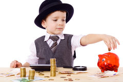 Boy at the table counts money. Little boy like a boss at the table counts money, isolated on white Royalty Free Stock Image