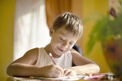 Boy at the table draws with crayons Stock Image