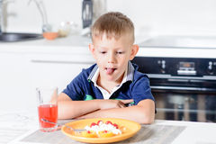 Boy at Table Looking at Plate of Cheese and Fruit Royalty Free Stock Image