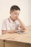 Boy and tablet. Bored with the tablet. Learn and play. stock photos