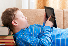 Boy with a tablet computer is on the books. In the room Stock Photography