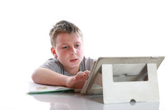Boy with tablet computer makes lessons Stock Photos
