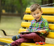 Boy with tablet computer in park Royalty Free Stock Photos