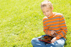 Boy with a Tablet Computer. School-age boy sitting on a green lawn in summer park, holding  tablet computer Royalty Free Stock Photo