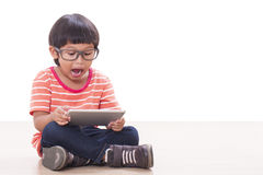 Boy with tablet. Cute boy playing a game on computer tablet Stock Image