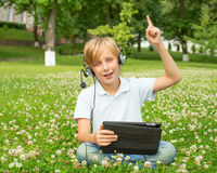 Boy with the tablet and headphones Stock Images