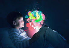 Boy with tablet in his bed. Teenage boy in pajamas lying in bed using tablet pc Royalty Free Stock Images