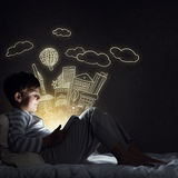 Boy with tablet in his bed. Teenage boy in pajamas lying in bed using tablet pc Royalty Free Stock Photos
