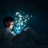 Boy with tablet in his bed. Teenage boy in pajamas lying in bed using tablet pc Stock Photos
