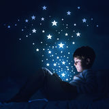 Boy with tablet in his bed. Teenage boy in pajamas lying in bed using tablet pc Royalty Free Stock Image