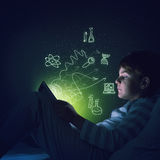 Boy with tablet in his bed. Teenage boy in pajamas lying in bed using tablet pc Royalty Free Stock Photo