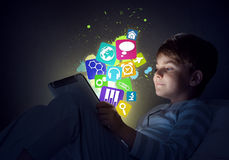 Boy with tablet in his bed. Teenage boy in pajamas lying in bed using tablet pc Stock Image