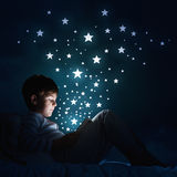 Boy with tablet in his bed. Teenage boy in pajamas lying in bed using tablet pc Stock Photo