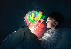 Boy with tablet in his bed. Teenage boy in pajamas lying in bed using tablet pc Stock Images