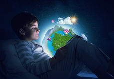 Boy with tablet in his bed. Teenage boy in pajamas lying in bed using tablet pc. Elements of this image are furnished by NASA Royalty Free Stock Photography