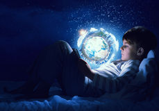 Boy with tablet in his bed. Teenage boy in pajamas lying in bed using tablet pc. Elements of this image are furnished by NASA Stock Image