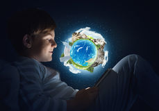 Boy with tablet in his bed. Teenage boy in pajamas lying in bed using tablet pc. Elements of this image are furnished by NASA Stock Photography