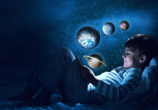 Boy with tablet in his bed. Teenage boy in pajamas lying in bed using tablet pc. Elements of this image are furnished by NASA Royalty Free Stock Photos