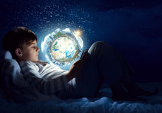 Boy with tablet in his bed. Teenage boy in pajamas lying in bed using tablet pc. Elements of this image are furnished by NASA Stock Images