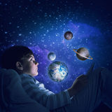 Boy with tablet in his bed. Teenage boy in pajamas lying in bed using tablet pc. Elements of this image are furnished by NASA Stock Photo