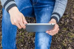 Boy with tablet in his hands sits on grass. Preparation for e stock images