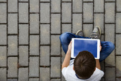 Boy with tablet outdoors. Child pc computer sitting on the pavement. Top view. Technology, addiction, sadness royalty free stock images
