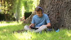 Boy with tablet at park stock video footage