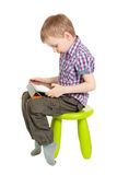 Boy with a Tablet PC. Sitting on a chair in the children's green studio isolated on white background Royalty Free Stock Image
