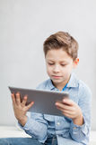 Boy with tablet pc. Boy sitting  in the living room using a tablet pc Royalty Free Stock Image