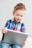 Boy with tablet pc. Boy sitting in the living room using a tablet pc Stock Image