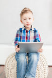 Boy with tablet pc. Boy sitting in the living room using a tablet pc Stock Photo