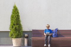 Boy with tablet PC and backpack sitting on the bench. Outdoor. Free copy spaceEducation, technology, people concept Royalty Free Stock Photo