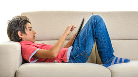 Boy with tablet pc lying on the sofa Stock Images
