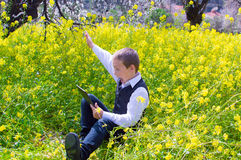 Boy with tablet pc outdoors. Boy sitting in the flower field using a tablet pc and rejoicing having won the game Royalty Free Stock Photo