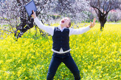 Happy boy received new tablet. Happy boy rejoicing in the flower field having received new tablet as present Stock Photos