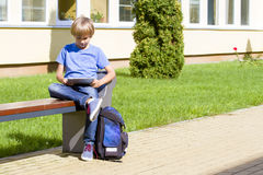 Boy with tablet PC sitting on the bench near school. Outdoor. Education, technology, people concept Stock Photos