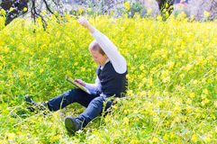 Boy with tablet pc. Boy sitting in the flower field using a tablet pc Stock Images