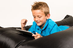 Boy with tablet and raised hand Stock Photos
