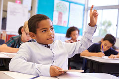 Boy with tablet raising his hand in elementary school class Royalty Free Stock Photography