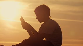 Boy with tablet at sunset sitting on the mountain stock video footage