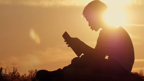 Boy with tablet at sunset sitting on the mountain stock footage