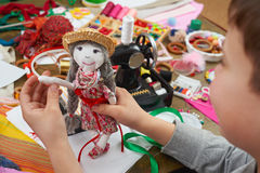 Boy tailor learns to sew, dress for doll, handmade and handicraft concept Royalty Free Stock Image