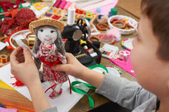 Boy tailor learns to sew, dress for doll, handmade and handicraft concept Royalty Free Stock Images