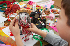 Boy tailor learns to sew, dress for doll, handmade and handicraft concept Stock Images