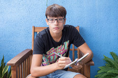 The boy takes notes in notepad Royalty Free Stock Photography