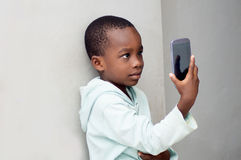 Boy takes photos with his phone. Royalty Free Stock Photography